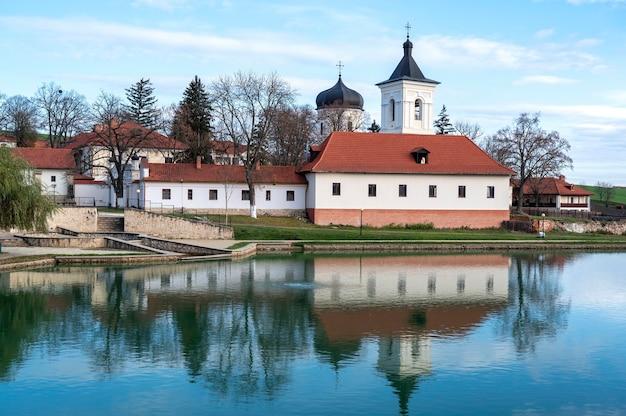 Vue du monastère de capriana. l'église en pierre, les bâtiments, les arbres nus. un lac au premier plan, beau temps en moldavie