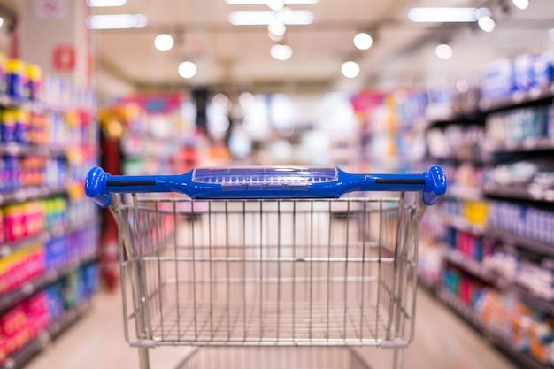 Vue du panier dans une allée de supermarchés avec des étagères de produit flou abstrait flou backg