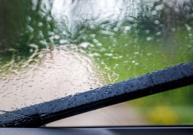 Vue du pare-brise et du balai d'essuie-glace depuis l'intérieur de la voiture dans la forêt