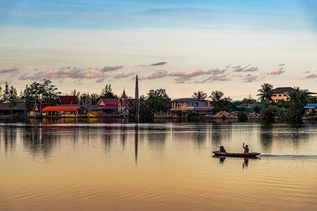 Vue du peuple roral avec bateau en rivière et coucher de soleil