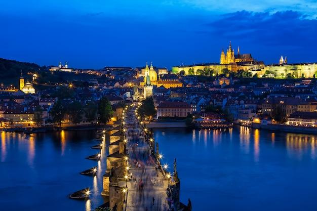 Vue du pont charles, du château de prague et de la vltava à prague, en république tchèque, pendant l'heure bleue