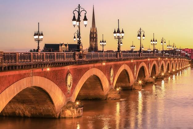 Vue du pont de pierre avec st michel churh à bordeaux au coucher du soleil