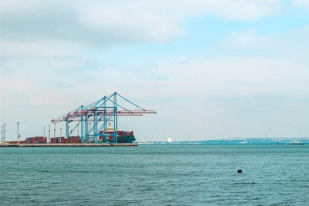 Vue du rivage au port avec des grues et des conteneurs.