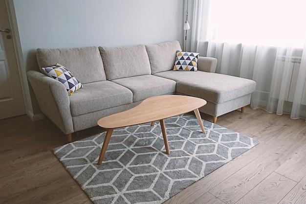 Vue du salon confortable et lumineux avec un canapé beige confortable