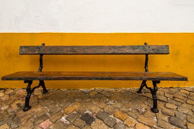 Vue du vieux banc de la rue à côté d'un mur blanc et jaune.
