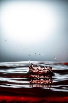 Vue de l'eau rouge éclaboussée de fond blanc.