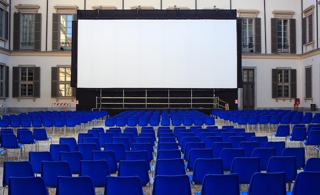 Vue de l'écran et des chaises bleues vides pour le cinéma en plein air