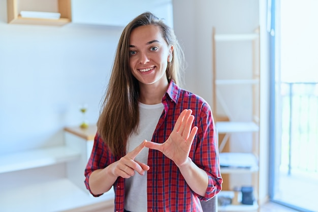 Vue d'écran de portrait de jeune fille mignonne heureuse souriante pendant des cours de langue des signes en ligne à la maison en utilisant la conférence webcam sur ordinateur