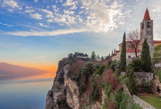 Vue de l'église chiesa di san giovanni battista de la ville tremosine . lac de garde dans les rayons du soleil couchant. lombardie, italie