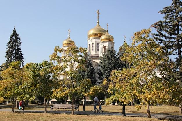 Vue de l'église orthodoxe blanche avec des dômes dorés dans le parc.