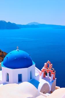 Vue avec l'église orthodoxe grecque avec des dômes bleus et un petit beffroi à oia sur l'île de santorin, grèce