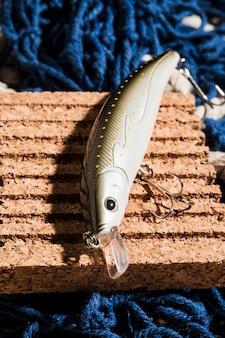 Une vue en élévation d'appâts de pêche avec un crochet sur une planche de liège au-dessus du filet de pêche bleu
