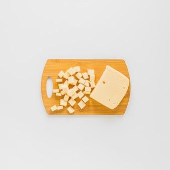 Une vue en élévation de cubes de fromage sur une planche à découper en bois sur fond blanc