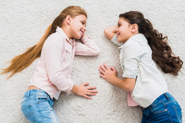 Une vue en élévation de deux filles souriantes allongées sur un tapis qui se regardent