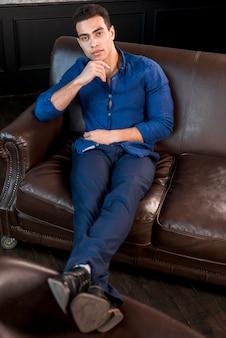 Une vue en élévation du beau jeune homme assis sur un canapé marron avec la main sur son menton en regardant la caméra