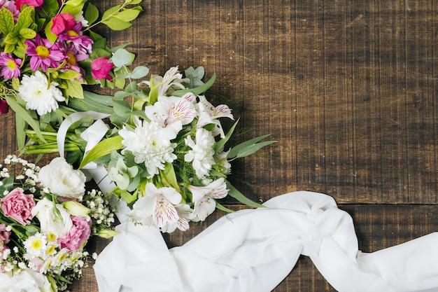 Une vue en élévation du bouquet de fleurs avec une écharpe blanche sur une table en bois