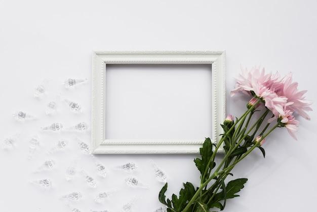 Vue en élévation du cadre d'image vide; coquilles de cristal et fleurs roses sur une surface blanche