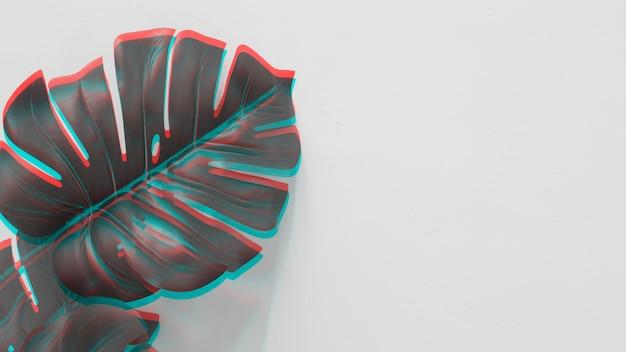 Une vue en élévation de la feuille de monstera avec une lumière rouge et turquoise sur fond blanc