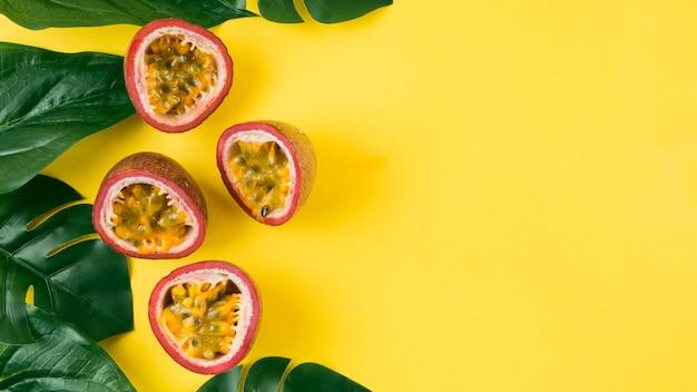 Une vue en élévation de feuilles vert artificielles et de fruits de la passion coupés en deux sur fond jaune