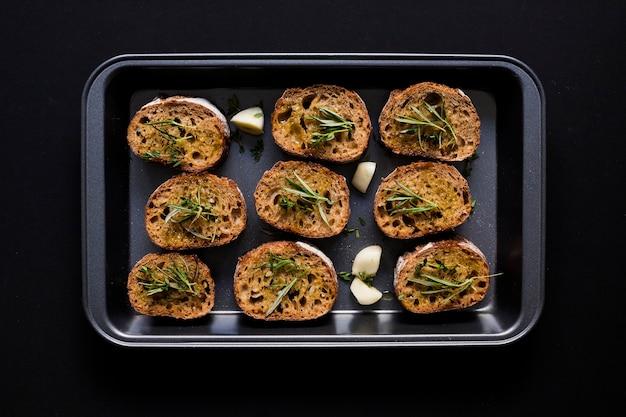 Une vue en élévation de pain grillé dans la plaque de cuisson sur fond noir
