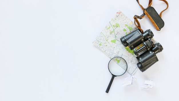 Vue en élévation d'un papier de soie froissé; carte; jumelles et loupe sur fond blanc