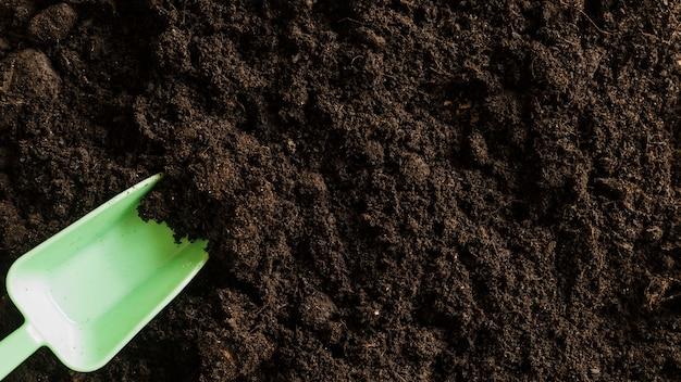 Une vue en élévation d'une pelle en plastique dans le sol fertile
