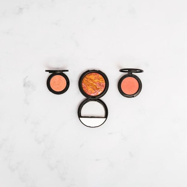 Une vue en élévation de la poudre de maquillage pour le visage sur un fond texturé en marbre
