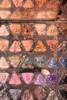 Vue en élévation de poudres de fard à paupières de forme triangulaire et brosse
