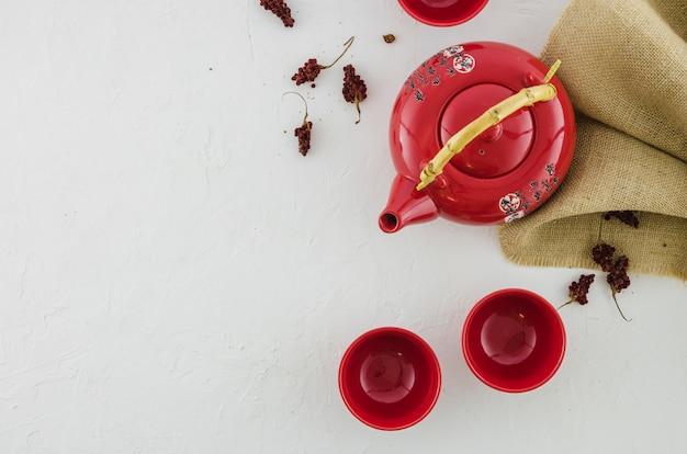 Une vue en élévation de la théière en céramique rouge et deux tasses sur fond noir