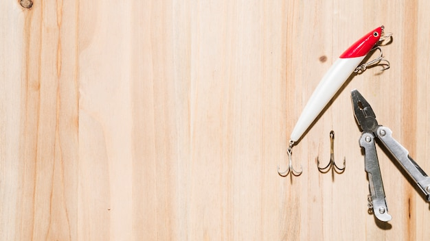 Une vue élevée d'appâts de pêche rouges et blancs avec un crochet et une pince sur un fond de surface en bois