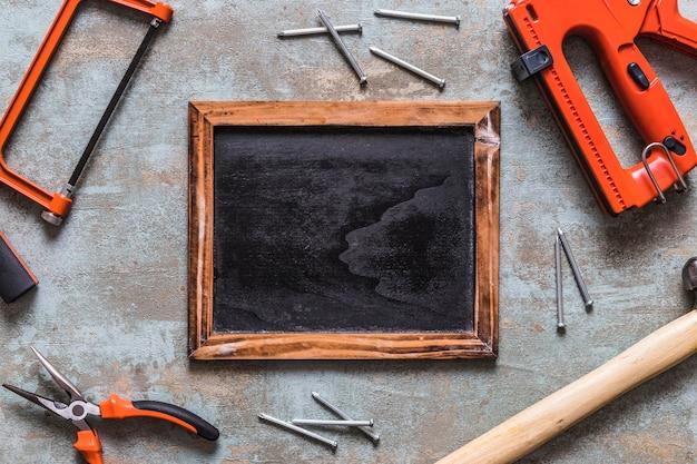 Vue élevée de l'ardoise vierge entourée de divers outils de travail