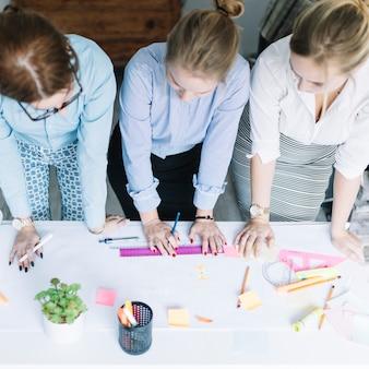 Vue élevée, de, businesswomen, planification, les, graphique entreprise, sur, papier, bureau