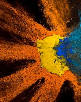 Vue élevée de la conception de poudre de holi jaune, orange et bleu sur fond noir