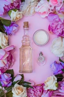 Vue élevée de la crème hydratante; bouteille d'huile essentielle et de parfum entourée de fleurs artificielles