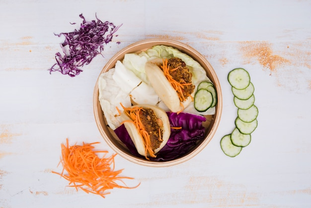 Une vue élevée de la cuisine traditionnelle de taiwan gua bao dans le paquebot avec salade sur fond de texture en bois