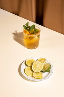 Vue élevée, de, délicieux, boisson, à, feuilles menthe, et, tranches citron vert, sur, plaque, sur, bureau blanc