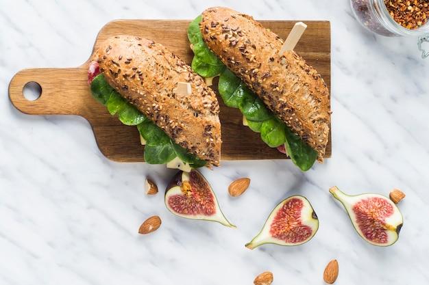 Vue élevée de délicieux hot dogs sur une planche à découper en bois près de tranches de figue; amandes et pot de flocons de piment sur marbre blanc