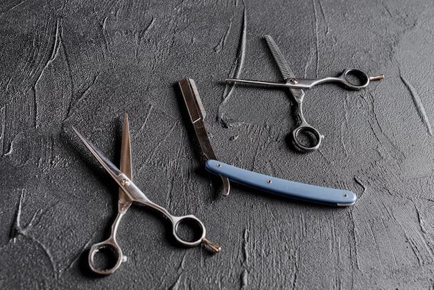 Vue élevée de deux ciseaux et rasoir sur fond noir