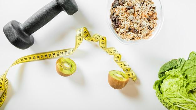 Vue élevée, de, diète alimentation, à, haltère, et, mètre-mesure, sur, toile de fond blanc