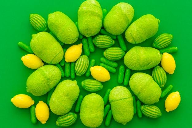 Vue élevée de divers bonbons sucrés sur la surface verte