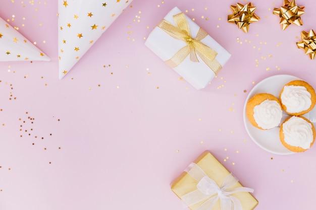 Une vue élevée du chapeau de fête; boite cadeau; arc et petit gâteau avec des confettis sur fond rose