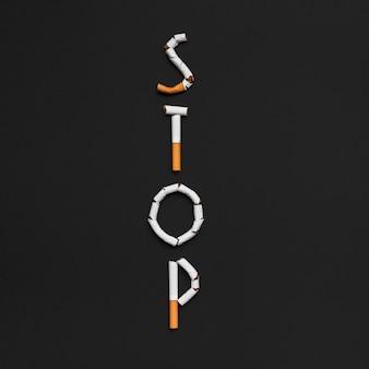 Vue élevée du mot d'arrêt fabriqué à partir d'une cigarette au-dessus d'un fond noir
