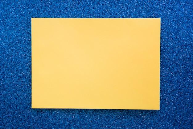 Vue élevée du papier carton jaune sur fond bleu