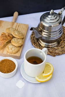 Vue élevée du thé au citron avec sucre brun et biscuit