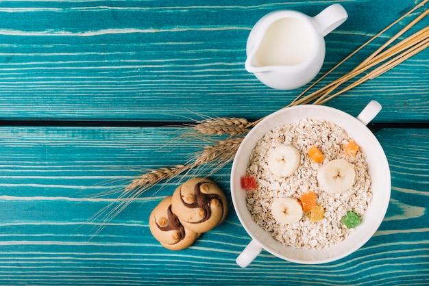 Vue élevée de farine d'avoine avec du lait et des biscuits sur la table