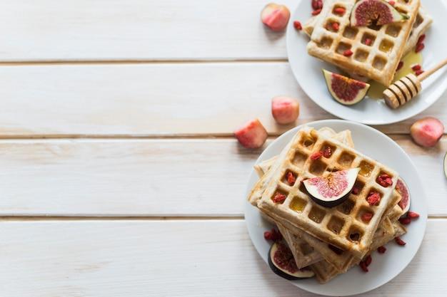 Vue élevée des gaufres belges; figue; mon chéri; et louche de miel servis dans l'assiette sur une planche