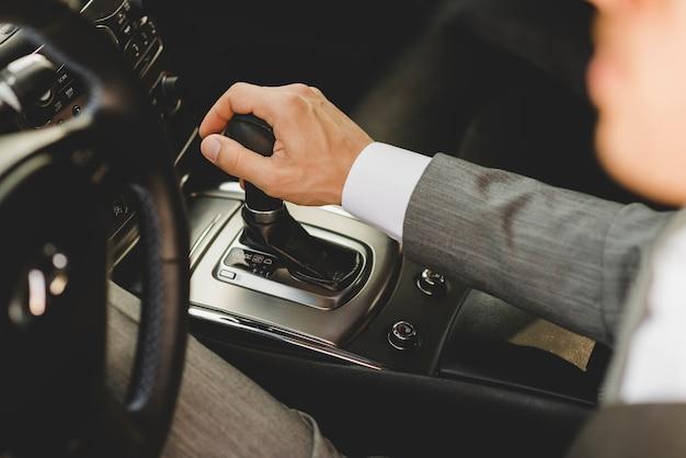 Vue élevée, de, homme affaires, conduite voiture, en mouvement, changement vitesse, transmission