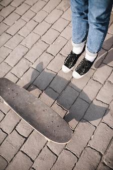 Vue élevée de la jambe et de la planche à roulettes du skateur sur le trottoir