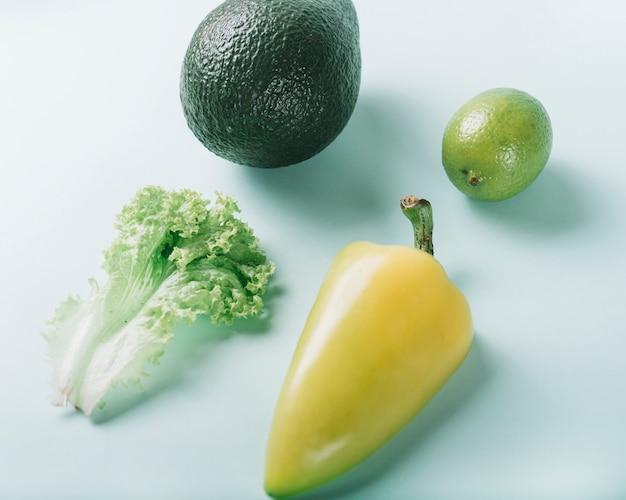 Vue élevée de la laitue; citron; avocat et poivron sur fond vert