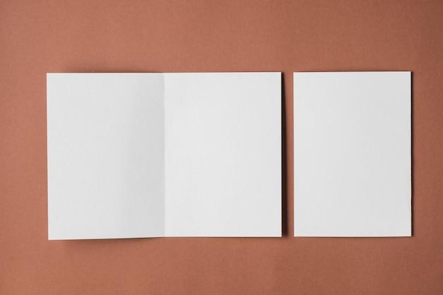 Vue élevée des livres blancs vierges sur fond marron